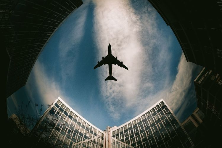 Low Angle View Of Airplane Flying Over Buildings In Sky