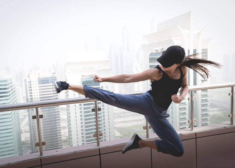 Young woman jumping against window