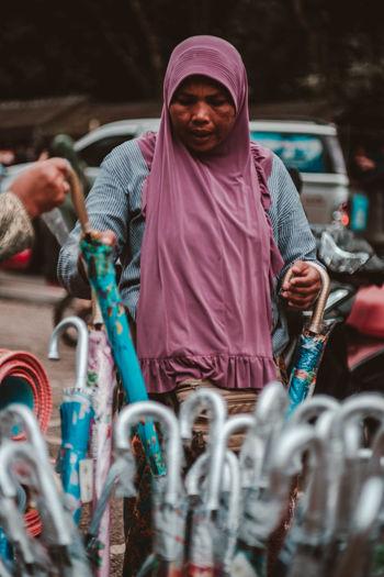 Female vendor selling umbrellas on road in city
