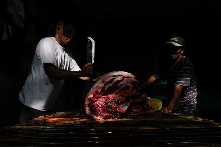 Butcher Cutting Meat In Dark Slaughterhouse