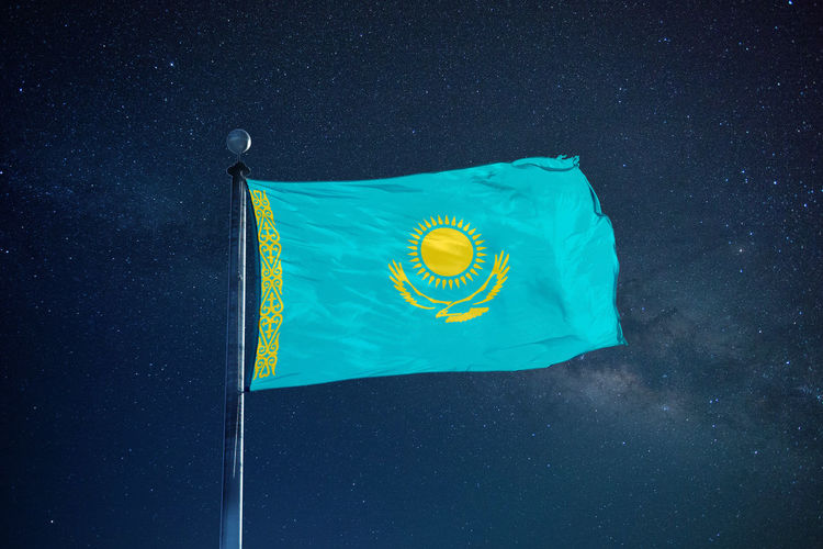 Low angle view of kazakhstan flag against star field sky