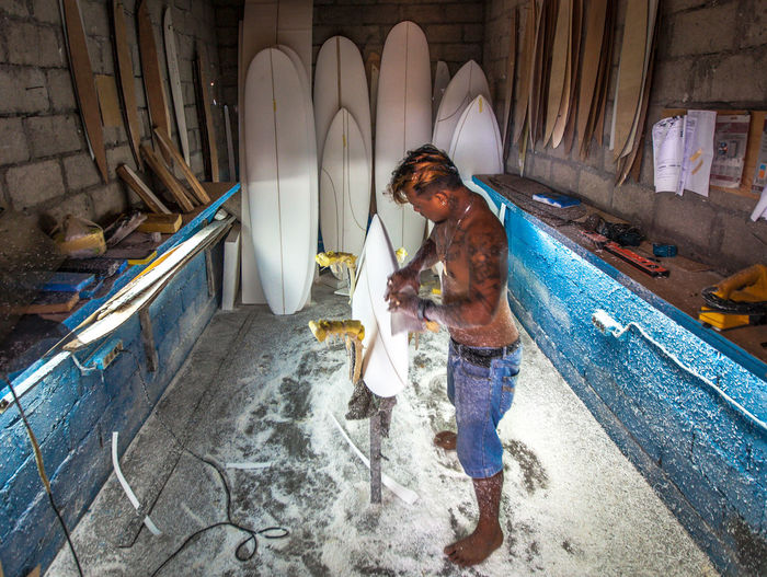 Surfboard shaping workshop in Bali with local shaper from Java Jeans Local Sanding Tattooed Workshop Blanks Fiberglass Fluorescent Light Foamposite Glassing Indoors  Lifestyles Manual Worker Men Occupation One Person Rack Real People Resin Sanding Paper Shaping Standing Surfboard Shaping Tools Working This Is Masculinity Modern Workplace Culture Small Business Heroes