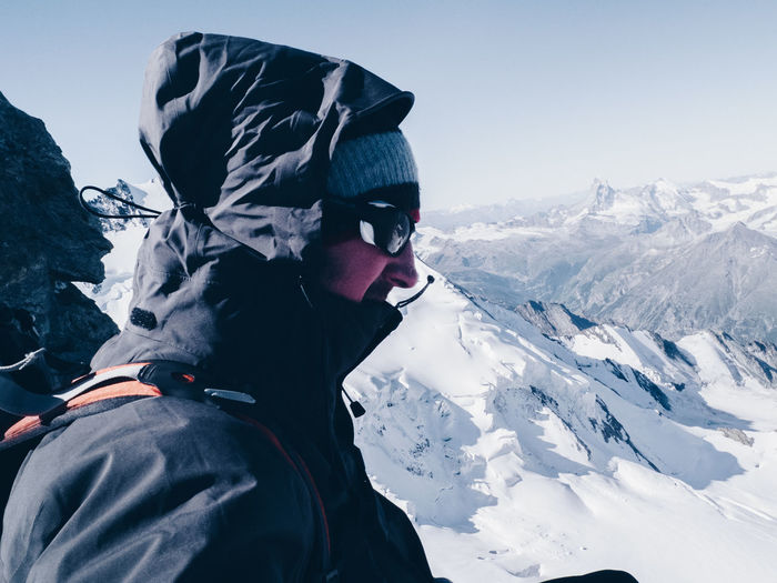 Side View Of Man In Warm Clothing Standing On Snow Covered Mountain