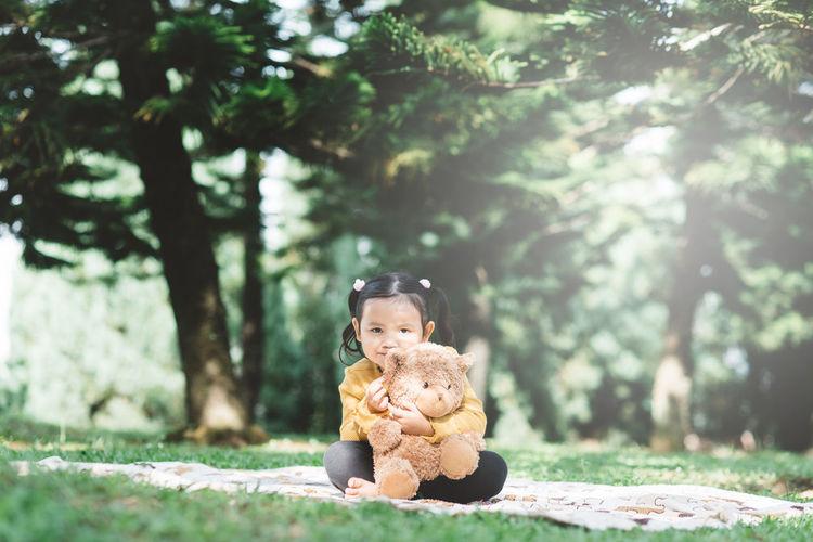 Cute boy sitting on toy against trees