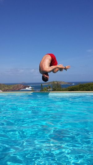 Man jumping in swimming pool against clear blue sky