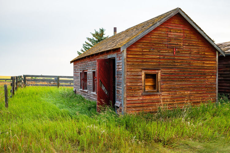 Abandoned Agricultural Building Architecture Building Building Exterior Built Structure Day Field Grass Green Color House Land Landscape Nature No People Outdoors Plant Rural Scene Sky Wood - Material