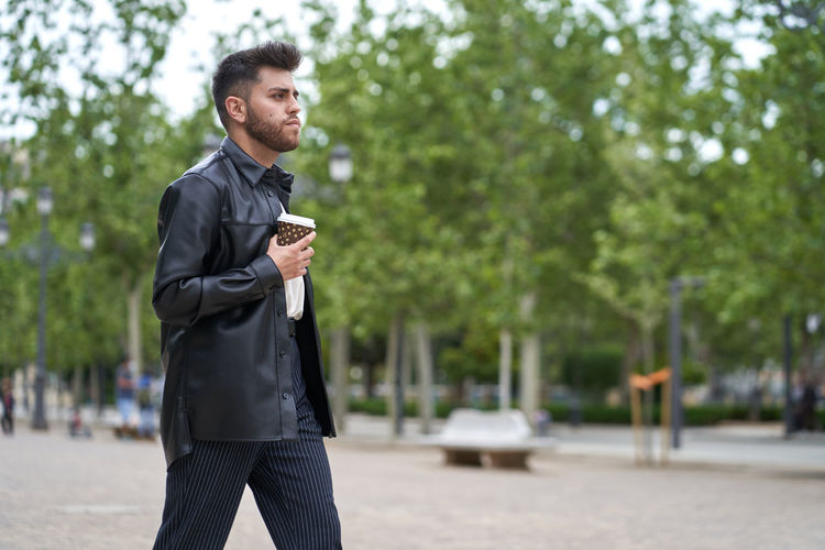 Young man holding reusable cup while walking in city