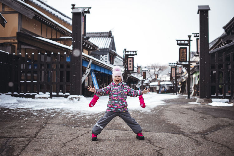 Architecture Arms Raised Building Exterior Built Structure Casual Clothing Child Childhood City Day Exiciting Front View Full Length Fun Human Arm Leisure Activity Nature Ninja Village One Person Outdoors Real People Warm Clothing Winter