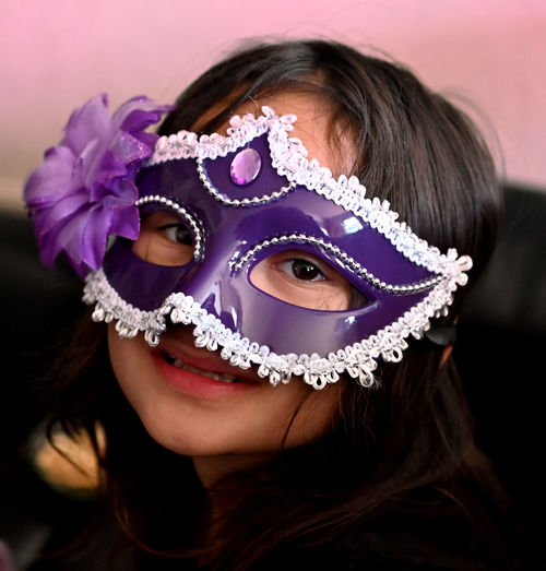 Close-up portrait of girl wearing masquerade mask