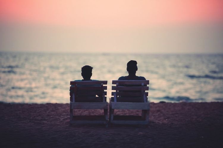 Rear View Of Couple Sitting On Chairs At Beach Against Sky During Sunset