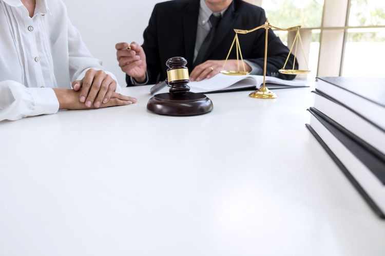 Midsection Of Lawyers Working At Desk In Courtroom