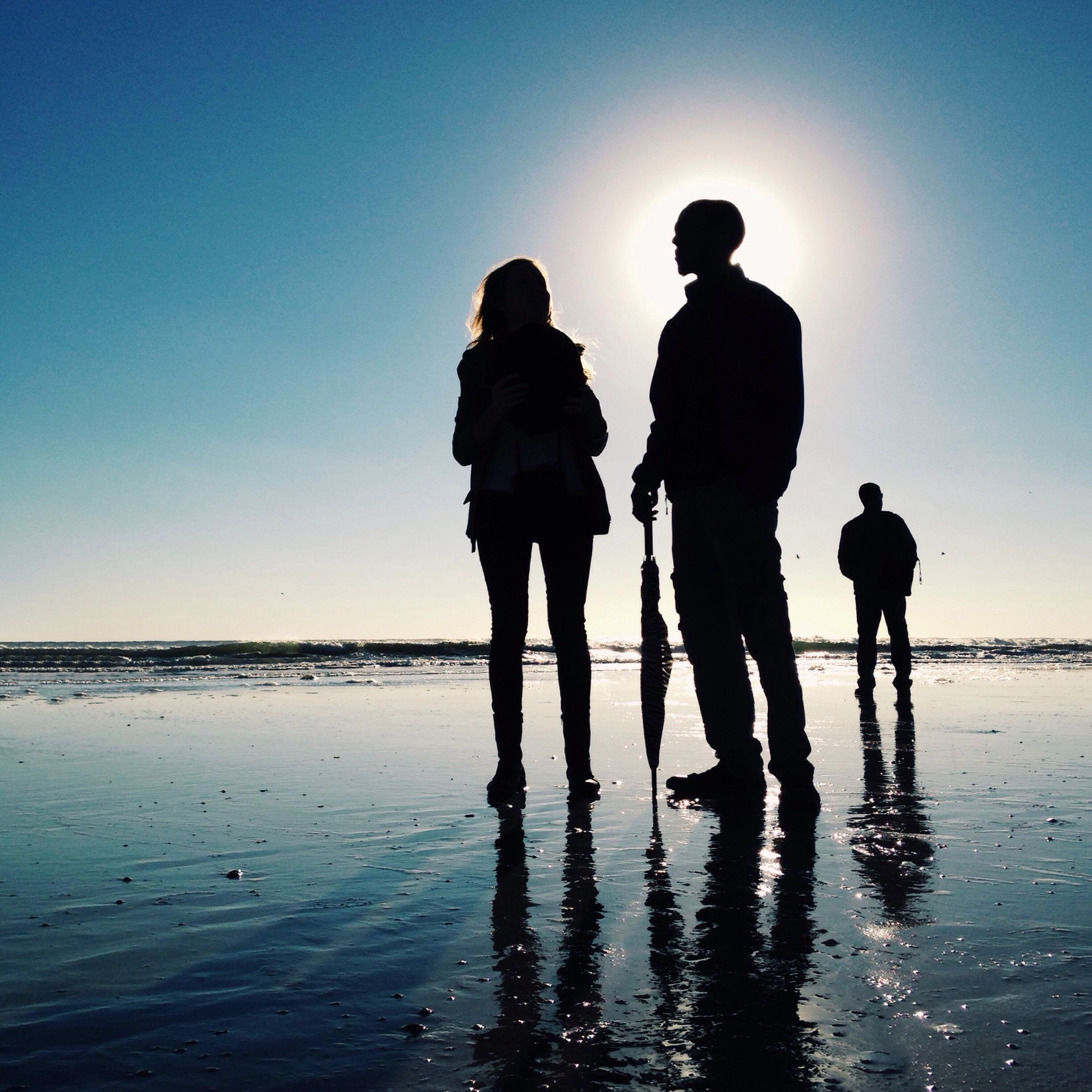 water, silhouette, sea, togetherness, clear sky, men, beach, leisure activity, lifestyles, standing, sunset, full length, reflection, shore, copy space, bonding, vacations, tranquility