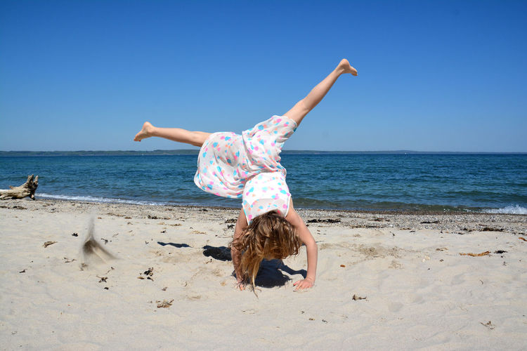 Girl doing a cartwheel on beach