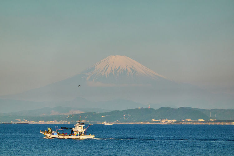 Boat sailing on sea by snowcapped mountain against sky