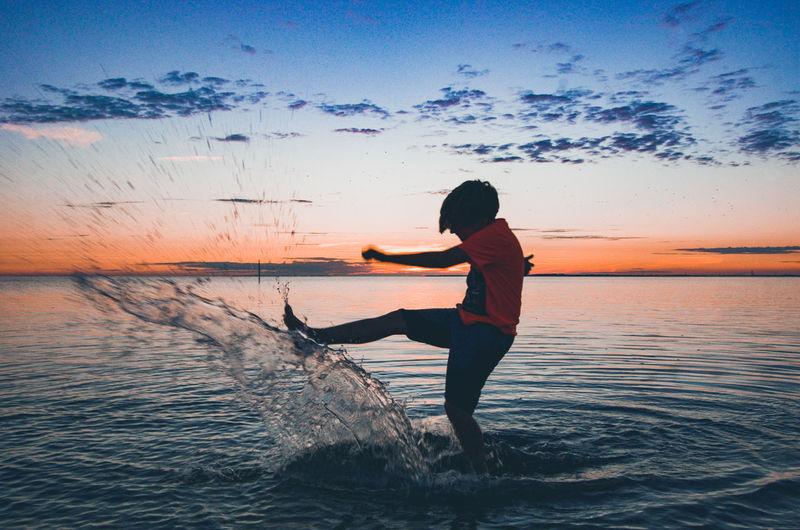 Boy Splashing Water In Sea Against Sky During Sunset