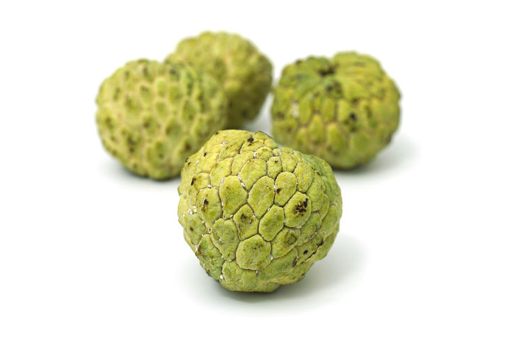 Close-up of green fruit against white background