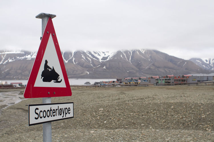 A snowmobile road sign in Longyearbyen, in the Norwegian arctic Norway Arctic Beauty In Nature Communication Danger Day Landscape Mountain Mountain Range Nature No People Outdoors Road Sign Scenics Sky Snow Snowcapped Mountain Text Triangle Shape Water
