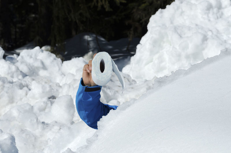 Cropped image of man holding toilet paper in snow