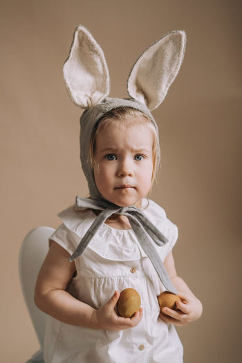 Toddler baby girl in funny hat with ears sitting with eggs in her hand