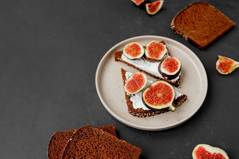 Triangular sandwiches with figs, cream cheese on black bread with seeds on flat porcelain plate