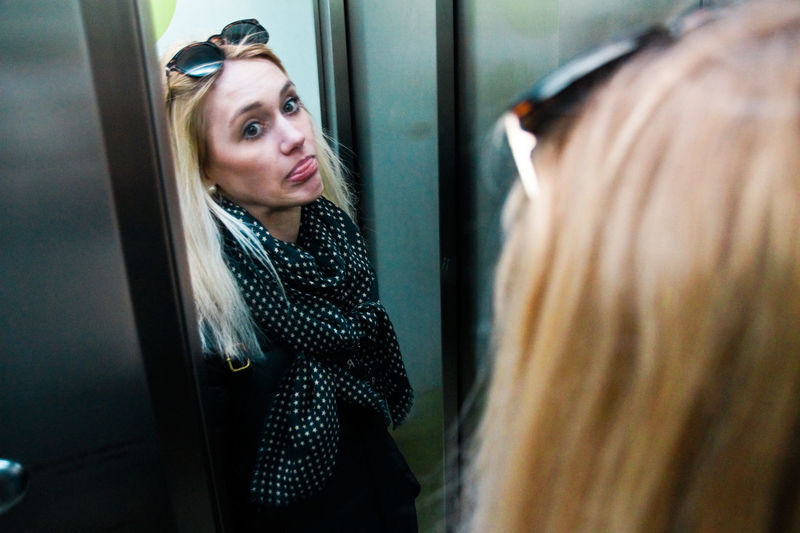 Reflection of young woman standing in elevator