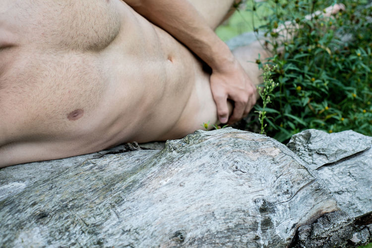 Low section of naked man relaxing on field