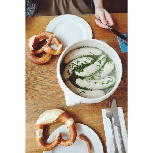 High angle view of woman eating fresh weisswurst and pretzel on table