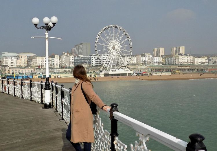 Woman Standing On Pier At Brighton Beach Against Sky