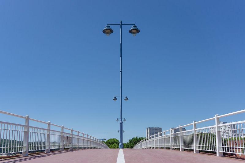 Street light on bridge against clear blue sky