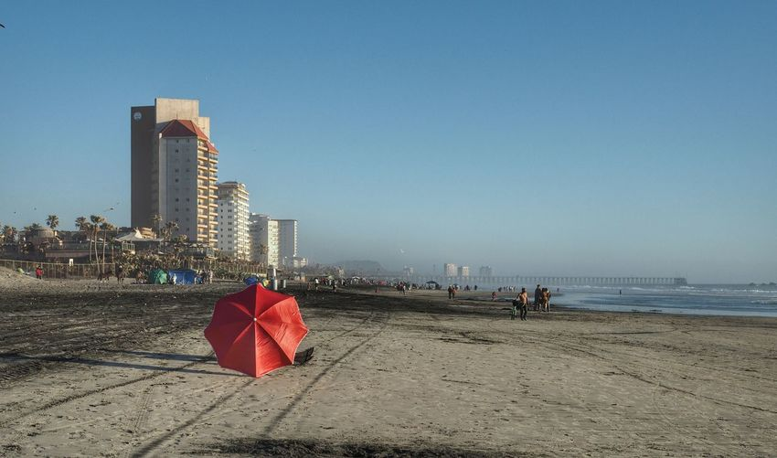 Red umbrella at sandy beach against clear blue sky