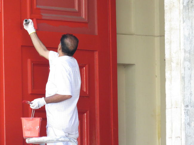 EyeEmNewHere Men In White Paint Red Door Architecture Built Structure Casual Clothing Day Door Entrance Holding Leisure Activity Lifestyles Men Mid Adult One Person Outdoors Painter Real People Rear View Red Red And White Red Color Standing Three Quarter Length