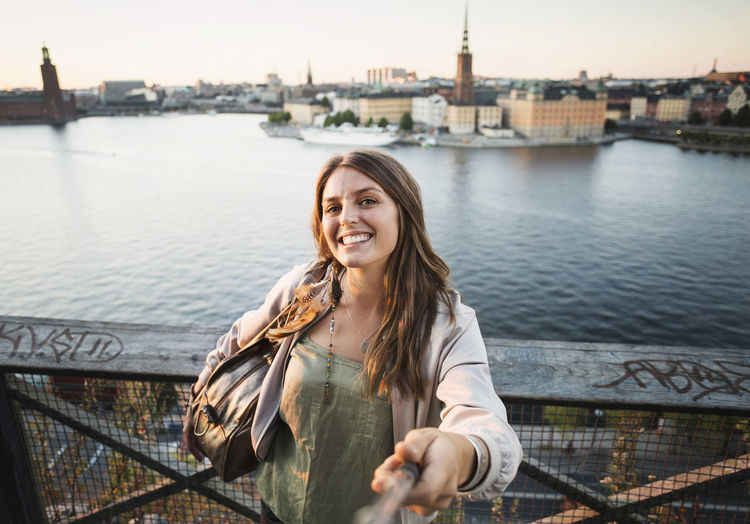 Portrait of smiling young woman by river in city