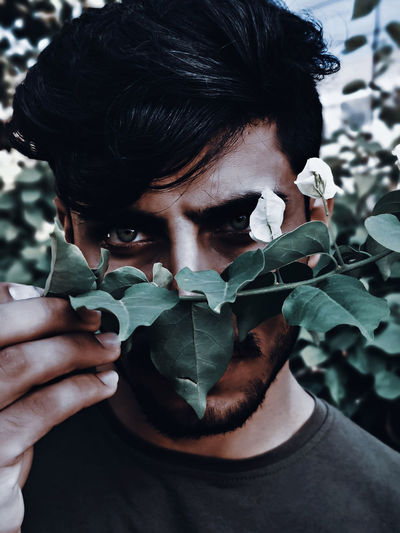 Close-up portrait of young man holding leaves