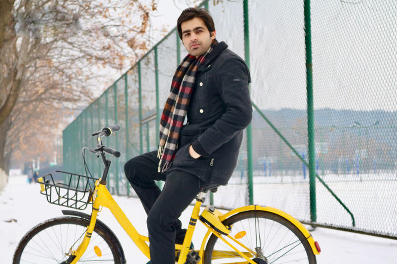 Side View Portrait Of Man Riding Bicycle During Winter