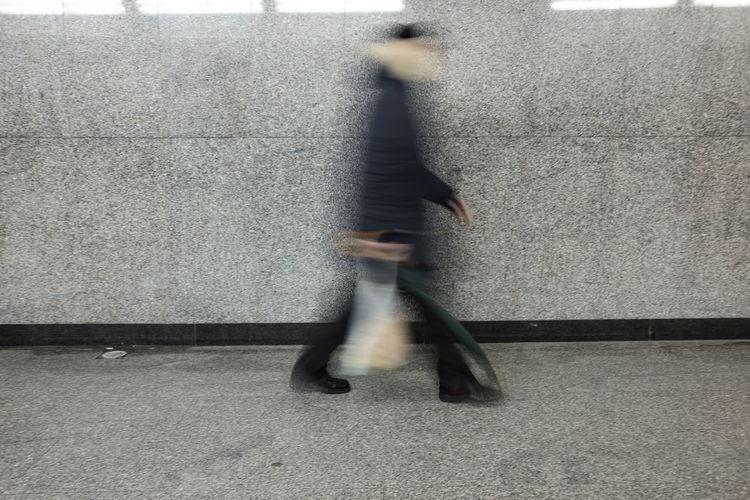 Blurred Motion Of Man Walking On Sidewalk