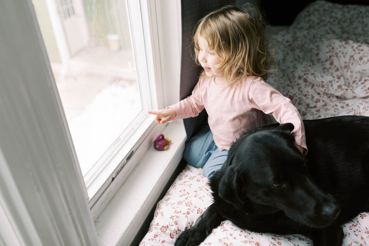 Girl looking away while sitting on window at home