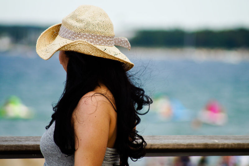 Side view of woman wearing sun hat standing at railing against sea