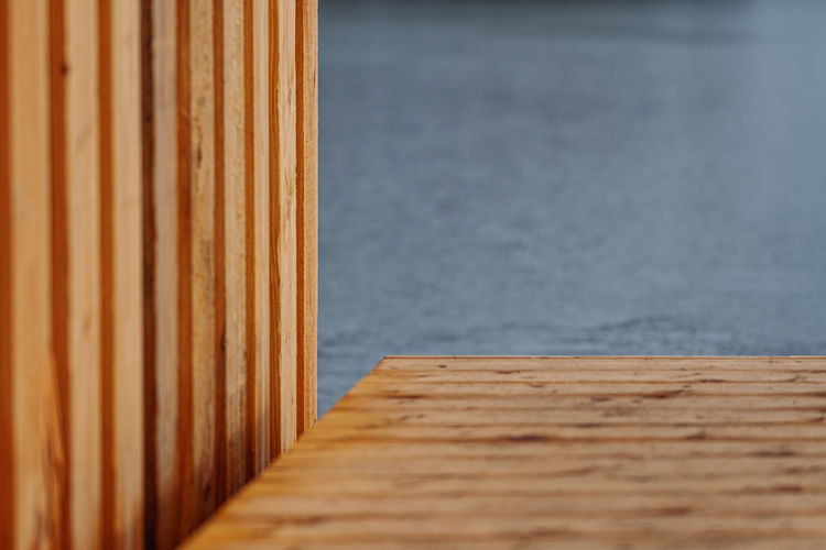 Close-up of wooden table against wall