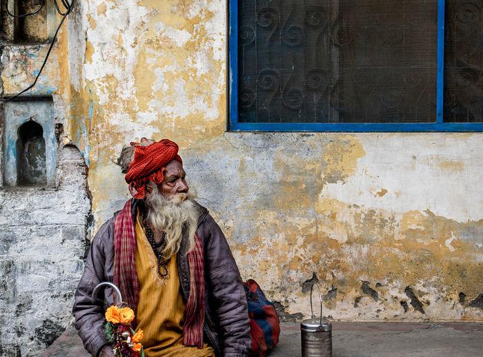 Sadhu sitting on sidewalk against house