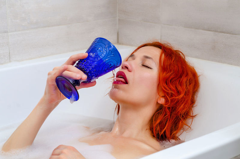 Portrait of young woman in drinking glass