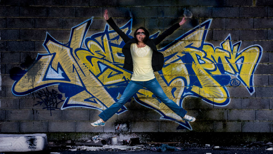 Full length portrait of young man jumping against wall
