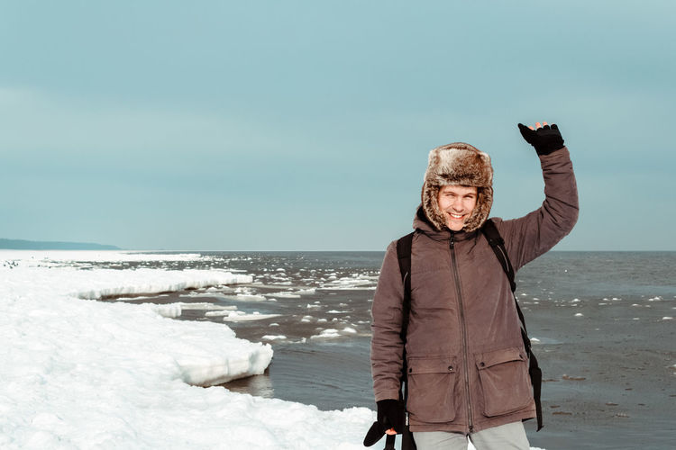 Portrait Of Man Standing On Frozen Lake Against Clear Sky