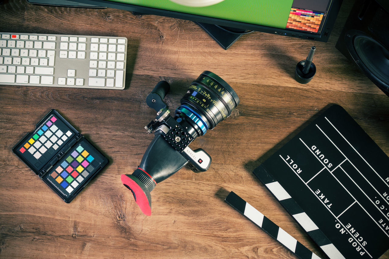 Directly above view of camera with film slate and computer on table
