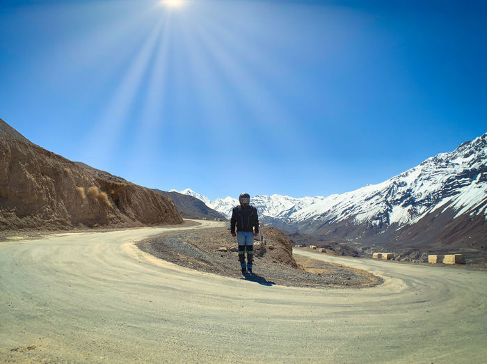 Rear view of man walking on mountain road against blue sky