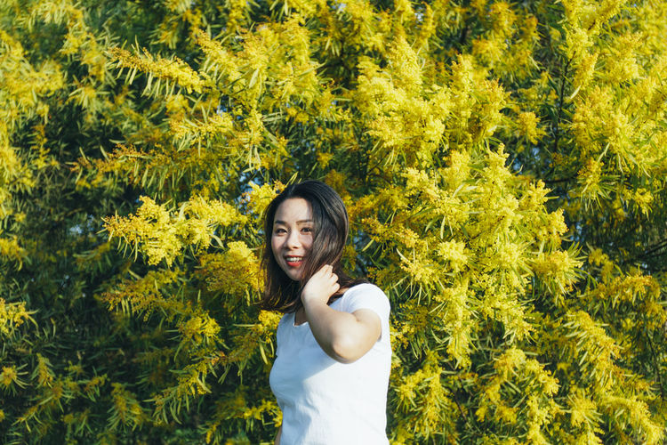 Portrait of young woman standing against yellow flowering tree