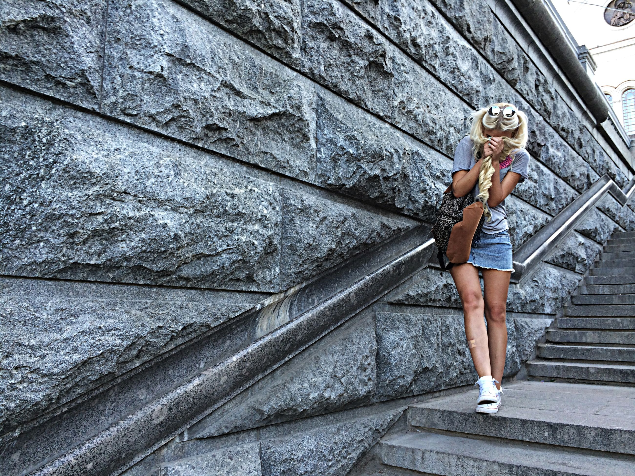 full length, lifestyles, young adult, casual clothing, standing, built structure, architecture, wall - building feature, person, leisure activity, young women, front view, steps, day, building exterior, outdoors, low angle view, side view