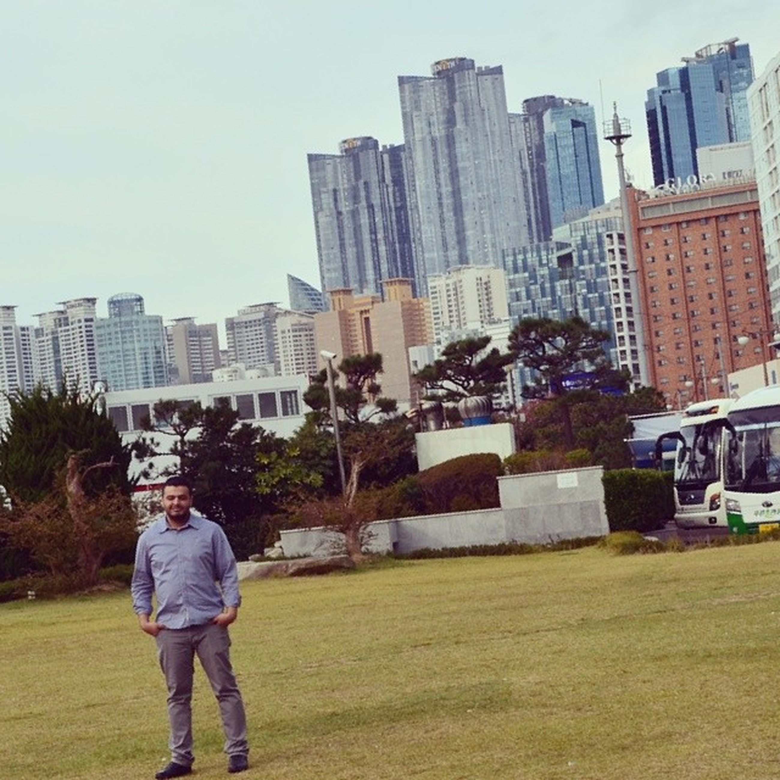 building exterior, architecture, built structure, city, lifestyles, grass, casual clothing, leisure activity, full length, rear view, men, sky, standing, tree, day, city life, building, person