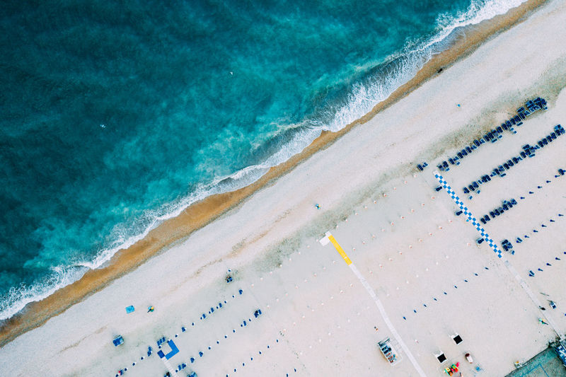 Top view of natural clear blue sea and white sand beach with umbrella