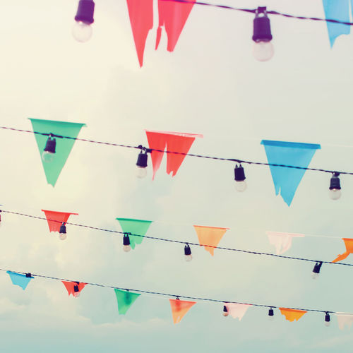 Colorful bunting flags and light bulbs on sky with retro filter effect Bunting Celebration Colorful Day Decoration Flag Flying Hanging Light Bulb Low Angle View Multi Colored Ornaments Outdoors Retro Styled Sky