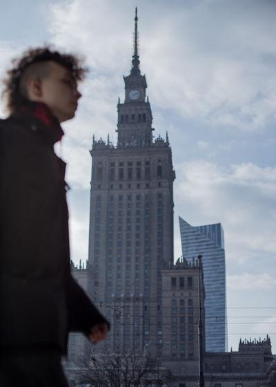 Man standing by buildings against sky in city